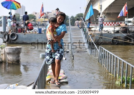 BANGKOK - NOV 4: An unidentified woman navigates a flooded riverside path on Nov 4, 2011 in Bangkok, Thailand. Approximately a fifth of the Thai capital is submerged under floodwater. - stock photo