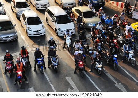 BANGKOK - NOV 14: Motorcyclists and cars wait at a junction during rush hour on Nov 14, 2012 in Bangkok, Thailand. Motorcycles are often the transport of choice for Bangkok's heavily congested roads. - stock photo