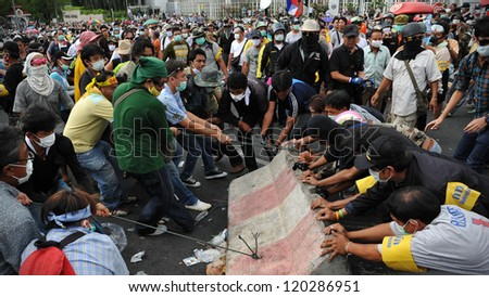 BANGKOK - NOV 24: Nationalist protesters from the Pitak Siam group remove concrete barriers from a police roadblock on during a large anti-government rally on Nov 24, 2012 in Bangkok, Thailand. - stock photo