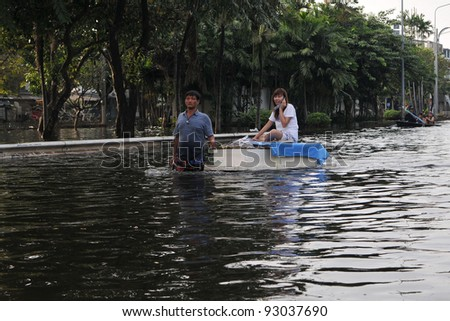 BANGKOK - NOV 4: Residents of Pinklao district make their way along a flooded section of road by boat as Thailand faces its worst flooding in 50 years on Nov 4, 2011 in Bangkok, Thailand. - stock photo