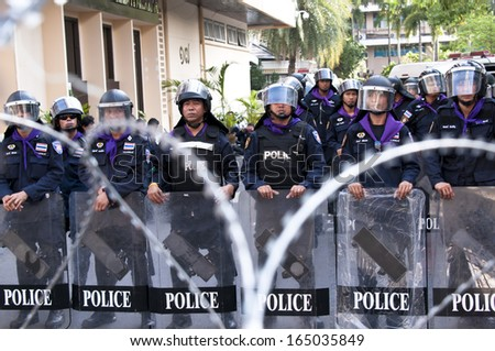 BANGKOK - NOV 28, 2013: Riot police stand guard at Royal Thai Police Headquarters during anti-government rally in Bangkok -  intensifying a demonstration aimed at toppling the prime minister. - stock photo