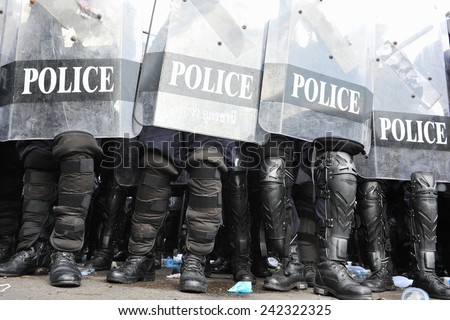 BANGKOK - NOV 24: Riot police stand guard during a violent anti government rally in the Thai capital on Nov 24, 2012 in Bangkok, Thailand. Protesters and police clashed repeatedly with dozens injured. - stock photo