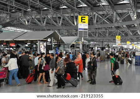 BANGKOK - NOV 13: Travelers gather at departures of Suvarnabhumi Airport on Nov 13, 2013 in Bangkok, Thailand. The airport is one of the busiest in Asia, handling about 45 million passengers per year. - stock photo