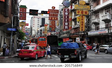 BANGKOK - NOV 22: Vehicles pass along Yaowarat Road in Chinatown on Nov 22, 2011 in Bangkok, Thailand. Yaowarat is the main street in Chinatown and was opened in 1891 in the reign of King Rama V. - stock photo