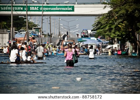 BANGKOK - NOVEMBER 13: A group of people evacuates from  the flooded area at Sapan Mai district during the massive flood crisis on November 13, 2011 in Bangkok. - stock photo