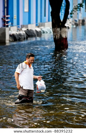 BANGKOK - NOVEMBER 5: An unidentified man walks through the flood on Phahonyothin Road during the worst flooding in Bangkok, Thailand on November 5, 2011.