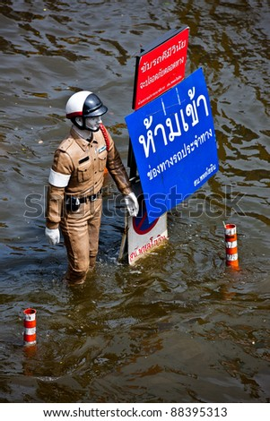 BANGKOK - NOVEMBER 5: The policeman statue stands on the road during the worst flooding in Bangkok, Thailand on November 5, 2011. - stock photo