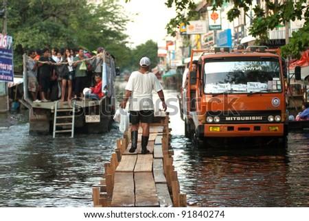 BANGKOK - NOVEMBER 30  : Villagers going home on the trucks and wood bridge during the flooding of November 30, 2 011 in Bangkok, Thailand. - stock photo