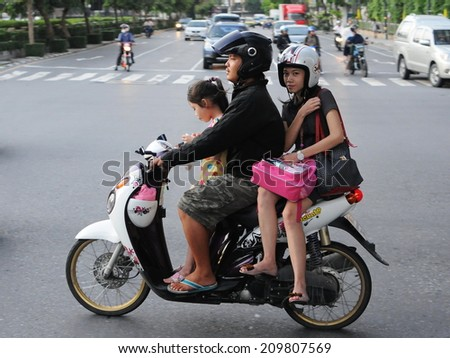 BANGKOK - OCT 17: An unidentified family travel by motorbike during rush hour on Oct 17, 2011 in Bangkok, Thailand. The use of motorbikes as family transport is commonplace in the Thai capital. - stock photo