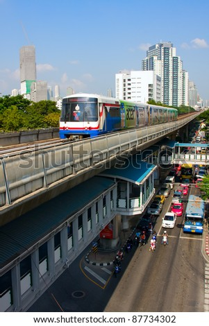 BANGKOK - OCT 25: BTS Skytrain on elevated rails above Sukhumvit Road on Oct 25, 2011 in Bangkok, Thailand. Each train of the mass transport rail network can carry over 1,000 passengers. - stock photo