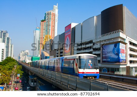BANGKOK - OCT 25: BTS Skytrain passes by on elevated rails above Sukhumvit Road on Oct 25, 2011 in Bangkok, Thailand. Each train of the mass transport rail network can carry over 1,000 passengers. - stock photo