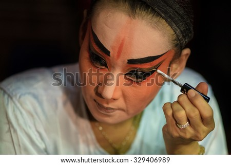 BANGKOK - OCTOBER 16: A Chinese opera actress painting mask on her face before the performance at backstage at major shrine in Bangkok's chinatown on October 16, 2015 in Bangkok,Thailand