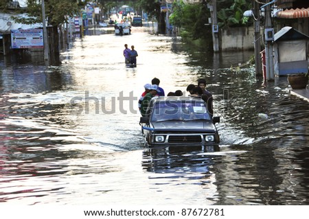 BANGKOK - OCTOBER 30: Unidentified people sit and stand in big truck to escape rising flood waters at Donmuang, in Bangkok, Thailand on Oct. 30, 2011 - stock photo