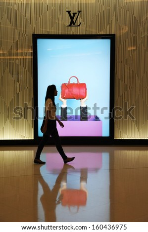 BANGKOK - SEP 26: An unidentified woman walks past a Louis Vuitton store in a shopping mall on Sep 26, 2013 in Bangkok, Thailand. Founded in 1854, Louis Vuitton had a revenue of $4.4 billion in 2012. - stock photo