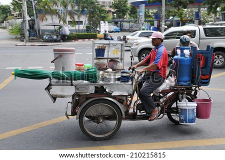 BANGKOK - SEPT 20: A vendor rides a mobile kitchen on a city street on Sept 20, 2011 in Bangkok, Thailand. Government statistics indicate 16,000 registered street vendors in the Thai capital. - stock photo