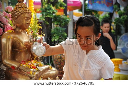 BANGKOK, THAILAND - APR 13, 2014: A temple goer pours water over a Buddha statue at a temple during a merit making ceremony to mark the traditional Thai New Year, which is also Songkran. - stock photo