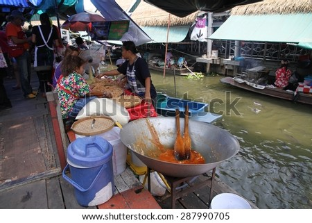 BANGKOK, THAILAND - April 12: A local Thai woman cooking in her boat at the Taling Chan Floating Market place in Bangkok, Thailand on the 12th April, 2015.