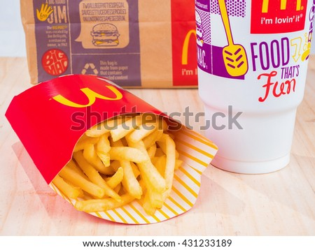 BANGKOK, THAILAND - APRIL 25, 2016: McDonald's meal on wooden background, includes coke cup, French Fries, on logo painted package. - stock photo
