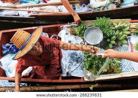 Bangkok, Thailand - April 15,2015: Old woman selling fruits and vegetables in a traditional floating market