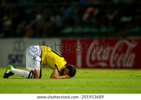 BANGKOK THAILAND-APRIL 05:Pokklaw Anan (yellow) of Police United  in action during Thai Premier League Bangkok United and Police United at Thai-Japanese Stadiumon Apr 05,2014 in Thailand - stock photo