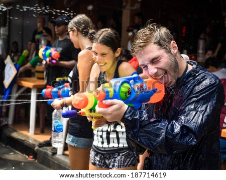 Bangkok, Thailand: April 15, 2014 - Tourists shooting water and having fun celebrating the traditional Thai New Year, Songkran, on Khao San Road in Bangkok, Thailand. - stock photo