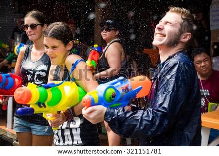 Bangkok, Thailand - April 15: Tourists shooting water guns and having fun at Songkran festival, the traditional Thai New Year, on Khao San Road in Bangkok, Thailand. - stock photo