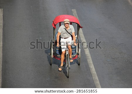 Bangkok, Thailand - April 16, 2015: Unidentified caucasian is riding a traditional tricycle on a street in the heart of Bangkok, Thailand. - stock photo