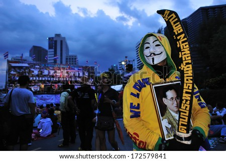 BANGKOK THAILAND- AUG 6: Protester  hold Thailand king photo and against government and Thaksin Shinawatra, former prime minister on August 6, 2013 in Lum Phini Park, Bangkok, Thailand. - stock photo