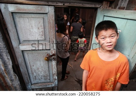 BANGKOK,THAILAND-AUG 12 : unidentified Thai poor boy smiling, when people come to his slum house.on August 12,2010 in Bangkok Thailand.