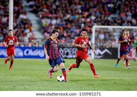 BANGKOK, THAILAND - AUGUST 7: Lionel Messi(L)of FC Barcelona in action during the international friendly match Thailand XI and FC Barcelona at Rajamangala Stadium on August7,2013 in,Thailand.   - stock photo
