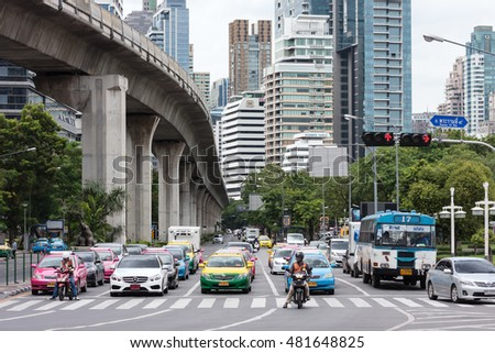Bangkok, Thailand - August 1, 2015: Picture of vehicles stop at the red light at Sala Daeng Junction and modern high rise buildings on Ratchadamri Rd. Bangkok's downtown