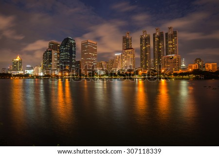 BANGKOK, THAILAND- AUGUST 12 : The business skyscraper skyline is in Bangkok city downtown with reflection on wide lake in Bangkok, Thailand on August 12, 2015