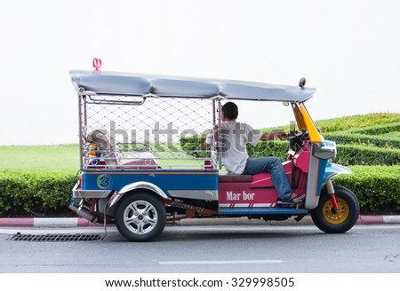 BANGKOK, THAILAND - AUGUST 10, 2015: Tuk tuk driver waiting for passenger at wall side of Grand palace.