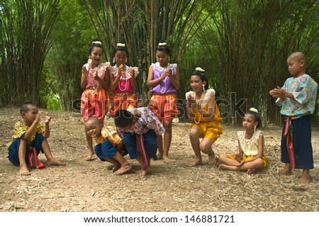 "BANGKOK,THAILAND-AUGUST 3:Unidentified boy and girl are playing ""Sit and collision"" which the ancient skits of Thailand's children in bamboo garden,on Aug.3,2009 in Bangkok,Thailand."
