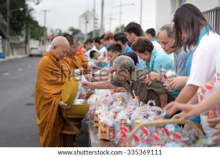 Bangkok, Thailand - August 12, 2015: Unidentified old woman in thai clothes Giving Alms to a Buddhist monk on Thai Mother Day. - stock photo