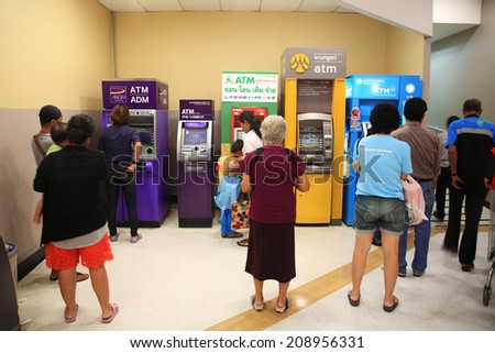BANGKOK, THAILAND - AUGUST 02, 2014: Unidentified people queuing to withdraw cash in ATM machine. Queue to use ATM is really dense for the beginning of each month. - stock photo