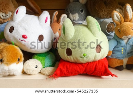 Bangkok, Thailand - Dec 25, 2016 : Many cute soft toys of rabbit plush dolls are displayed on the shelf including Peter Rabbit, selective focus on the green bunny. Editorial Used Only