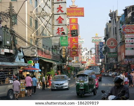 Bangkok, Thailand � December 22, 2013 � A view of China Town in Bangkok, Thailand.  Street vendors, pedestrians of both locals and tourists, and shoppers in China Town. There are cars on the road. - stock photo