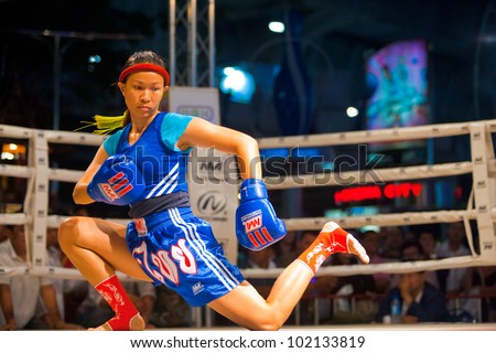 BANGKOK, THAILAND - DECEMBER 8, 2010: An unidentified female muay thai kickboxer performs a kicking routine in a kickboxing ritual called the wai khru on December 8, 2010 in Bangkok, Thailand - stock photo