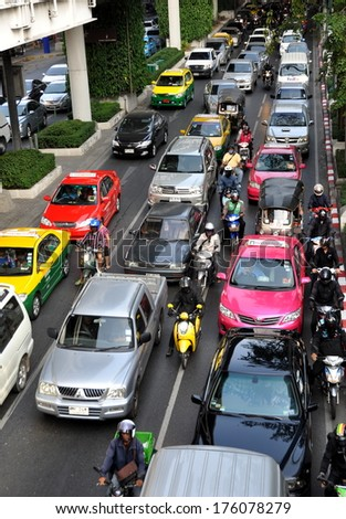Bangkok, Thailand  December 24, 2013:  Bumper-to-bumper cars, taxis, and vans on Sukhamvit Road during the evening rush hour