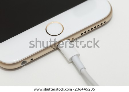 BANGKOK, THAILAND -DECEMBER 9, 2014: close up image of the new apple iphone6 with the charging cable on December 9, 2014 in Bangkok Thailand. - stock photo
