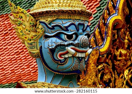 Bangkok, Thailand - December 24, 2005:  Detail of the face of a giant blue Yak guardian demon statue at Wat Phra Kaeo in the Royal Palace compound