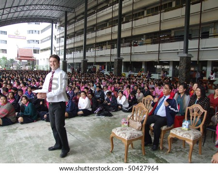 BANGKOK, THAILAND - DECEMBER 21 : English teacher gives speech while students sit outside for assembly at Seekan school December 21, 2005 in Bangkok. - stock photo