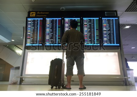 Bangkok, Thailand - December  5, 2014: Male  traveler with suitcase  is looking up information on flight departure board at Suvarnabhumi airport - stock photo