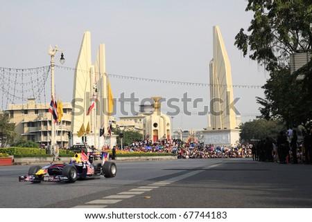 BANGKOK,THAILAND - DECEMBER 18: Mark Webber of Red-Bull Racing Team speeding shows with democracy monument on Ratchadamnoen road Bangkok 2010 ,December 18, 2010 in Bangkok,Thailand - stock photo