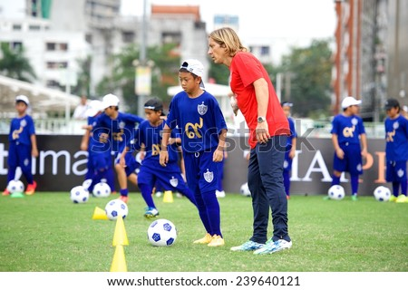 BANGKOK,THAILAND - DECEMBER 04:Michel Salgado (red)poses with local child at the Global Legends Series coaching clinic, at the Thailand Sports Authority, on December 4, 2014 in Bangkok, Thailand. - stock photo