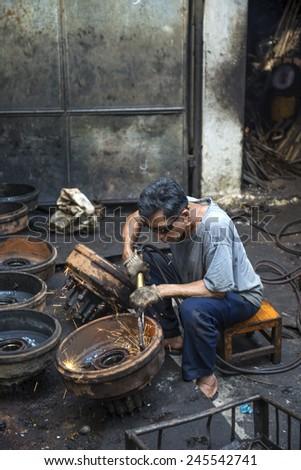 BANGKOK, THAILAND - DECEMBER 25, 2014: Street Photography of  auto  mechanic repairs old rims. - stock photo