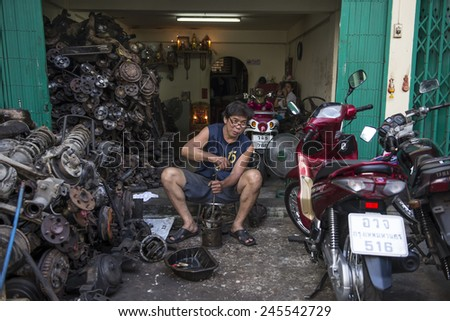 BANGKOK, THAILAND - DECEMBER 25, 2014: Street Photography of owner of a small body shop repairs scooter. - stock photo
