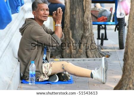 BANGKOK, THAILAND - DECEMBER 7 2008: Thai crippled man sits on the roadside begging for money on Khaosarn road. December 7 2008 in Bangkok. - stock photo
