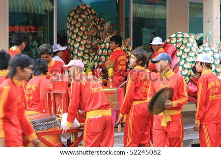 BANGKOK, THAILAND - DECEMBER 23 : Thai people dressed in red parade down a road in Bangkok suburbs in preparation for Chinese New Year. December 23 2009 in Bangkok.